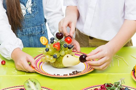 Copii ce realizeaza un arici din fructe