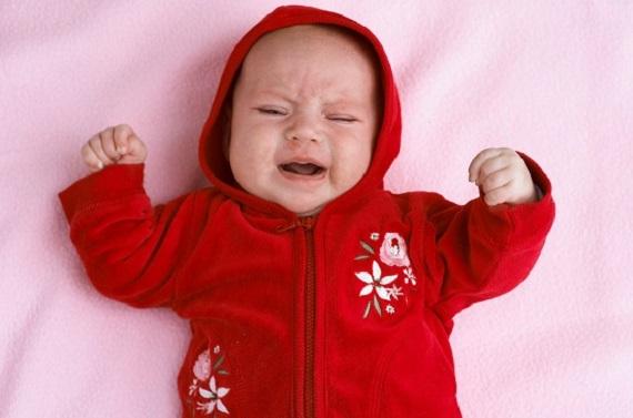 Bebelus care plange, cel mai probabil din cauza colicilor