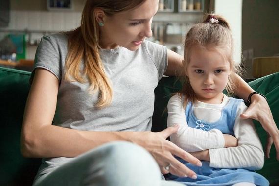 Mama care incearca sa stea de vorba cu fetita ei, care este suparata
