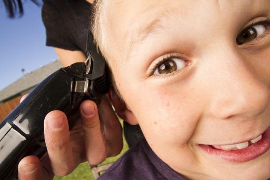 Copil ce este tuns cu masina