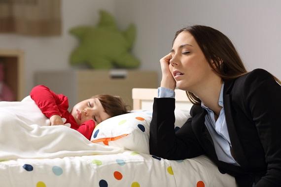 Mama ce a adormit stand langa patul copilului ei