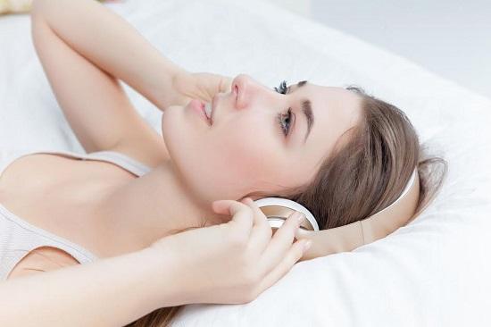 Femeie ce se relaxeaza cu castile la ureche