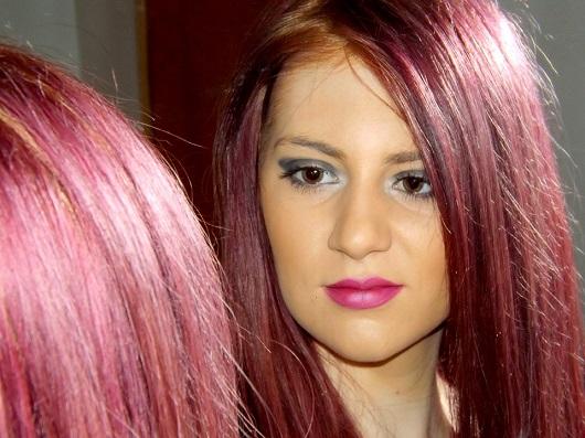 Fata cu parul vopsit in nuante de roz se uita in oglinda