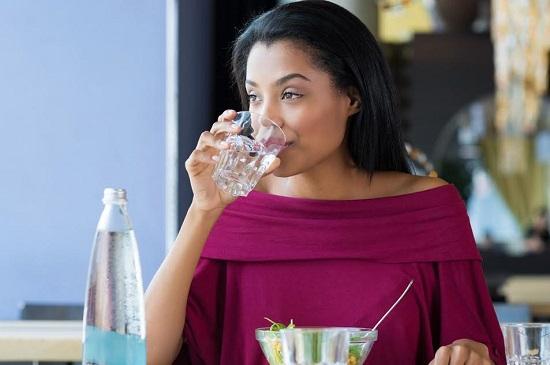 Femeie la masa, ce bea un pahar cu apa