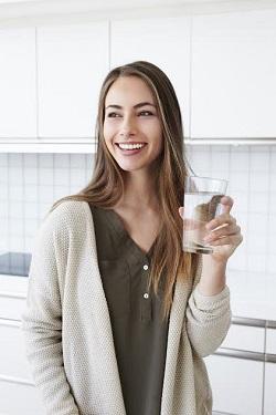 Femeie tanara, cu un pahar cu apa in mana