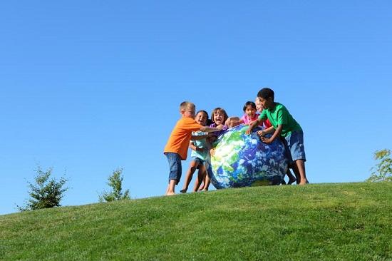 Copiii ce vor sa rostogoleasca o minge mare