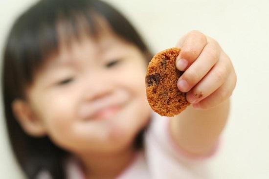 Fetita cu un cookie in mana
