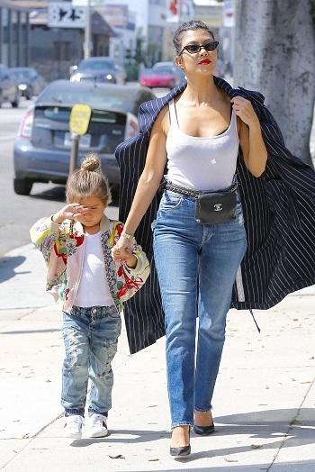Mama in blugi, mergand de mana cu fetita ei