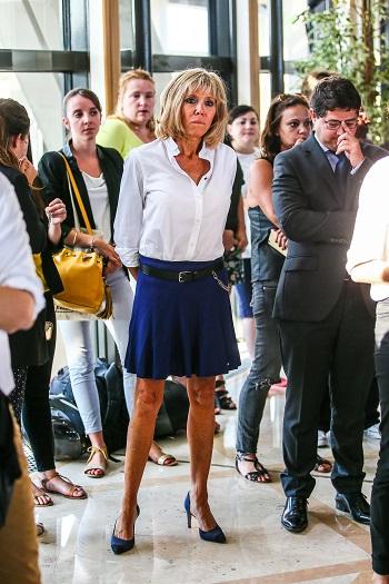 Brigitte Macron imbracata cu o camasa alba si cu o fusta scurta, albastra