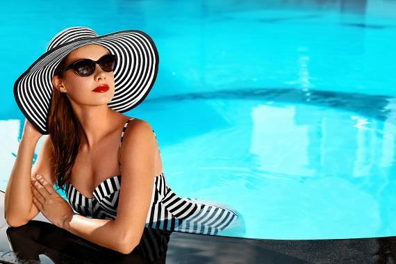 Femeie ce poarta o palarie de soare si sta la piscina
