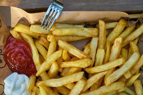 Cartofi prajiti alaturi de ketchup si alt sos alb