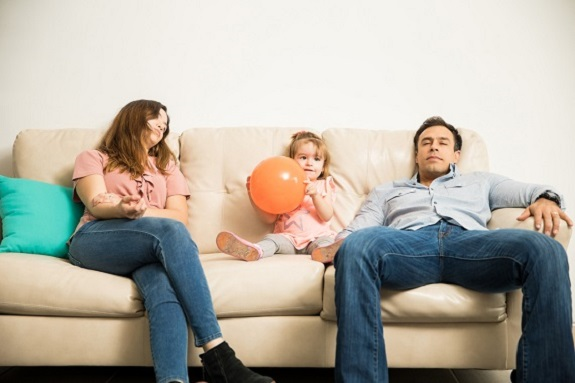Parinti epuizati, pe canapea, in timp ce fiica lor ar vrea sa se joace