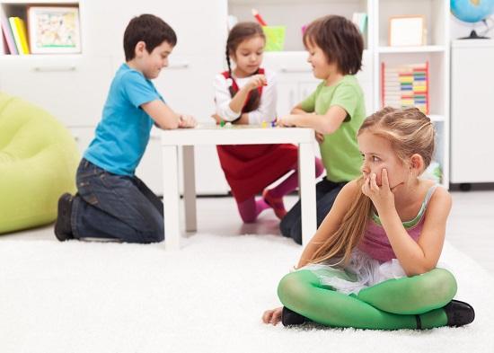 Copii ce se joaca la masa si o fetita ce sta izolata de ei