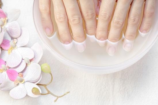 Femeie ce isi inmoaie unghiile pentru manichiura