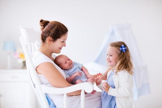 Fetita ce sta in fata mamei si fratiorului ei, nou-nascut