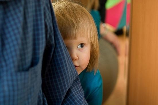 Copil rusinos, ce se ascunde in spatele unui adult