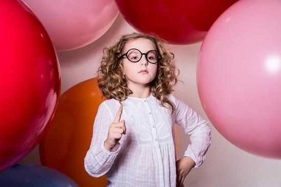 Fetita cu ochelari, inconjurata de baloane