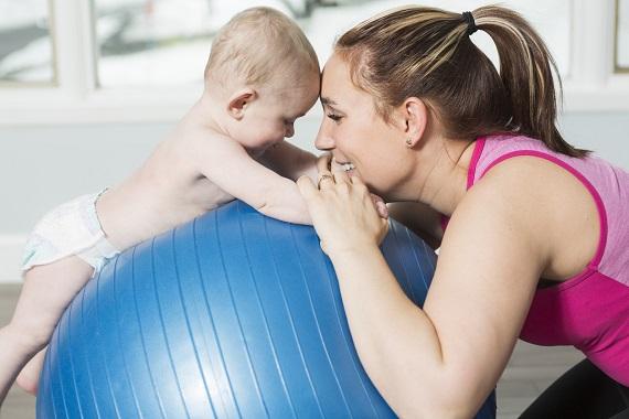 Mama ce si-a pus bebelusul pe o minge de gimnastica