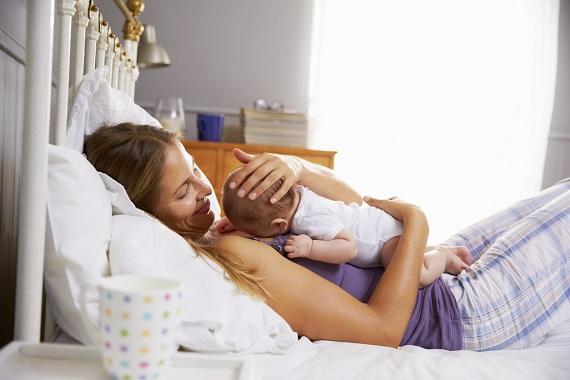 Mama in pat, tinandu-si bebelusul la piept