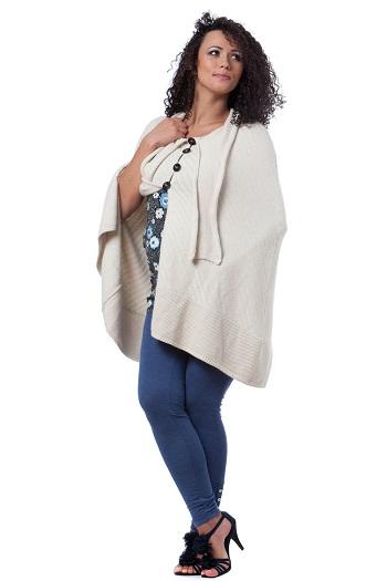 Femeie imbracata cu o pelerina tricotata si cu blugi