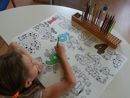 Fetita care coloreaza cifre de pe o plansa reutilizabila, din silicon