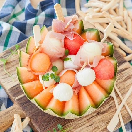 Prosciutto, mozzarella si bile de pepene galben si rosu, asezate pe un pepene galben