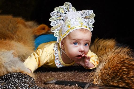 Bebelus ce sta pe o bucata de blana, langa o sabie