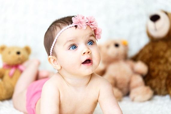 Fetita ce poarta pe cap o bentita cu flori roz