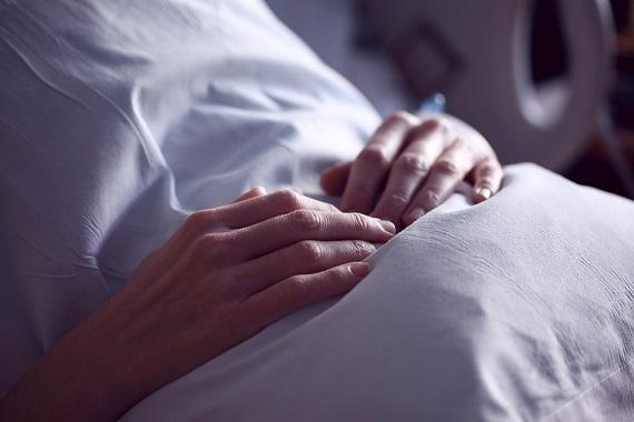 Femeie aflata pe un pat de spital