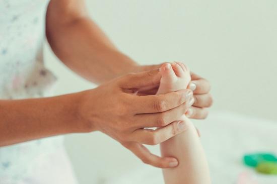 Femeie ce maseaza degetul mare al bebelusului