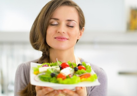 Fata ce se bucura de aromele din salata