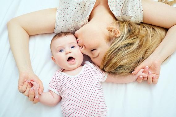 Mama ce isi saruta bebelusul pe un obrajor