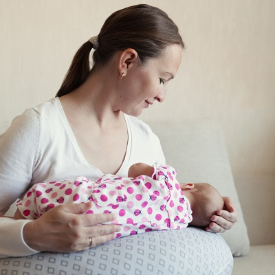 Mama ce alapteaza cu ajutorul unei perne de alaptare
