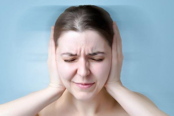 Femeie ce isi tine mainile la urechi din cauza unui disconfort