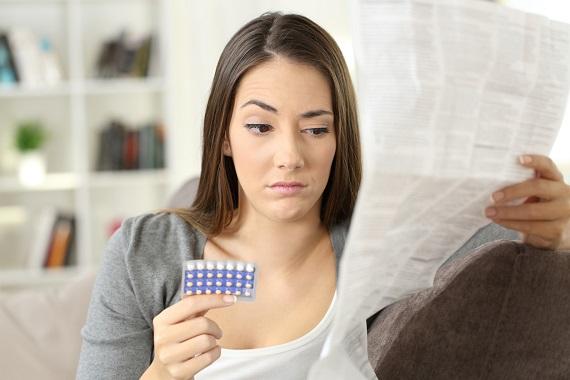 Tanara ce se uita ingrijorata peste un prospect la medicamente