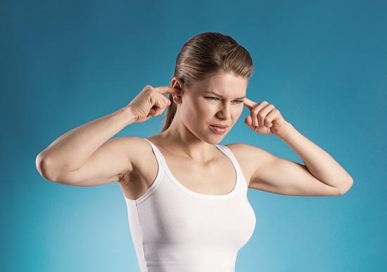 Femeie ce isi tine un deget intr-o ureche, din cauza disconfortului