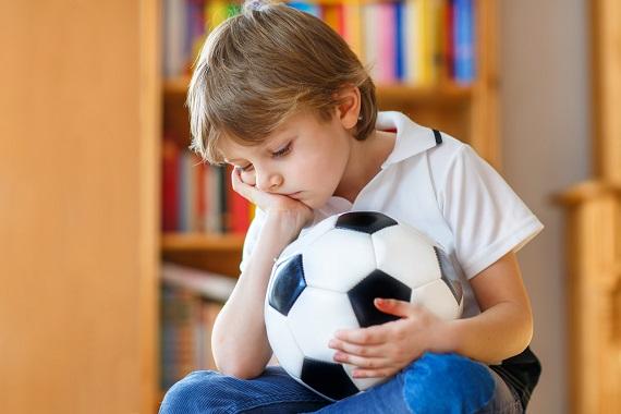 Baietel foarte trist, cu o minge de fotbal in mana