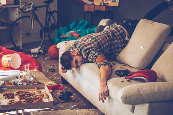 Barbat care sta in dezordine si a adormit pe canapea