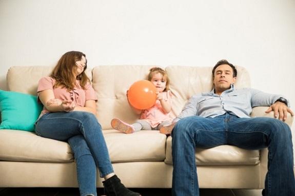 Parinti epuizati pe canapea, in timp ce fiica lor este dornica de joaca