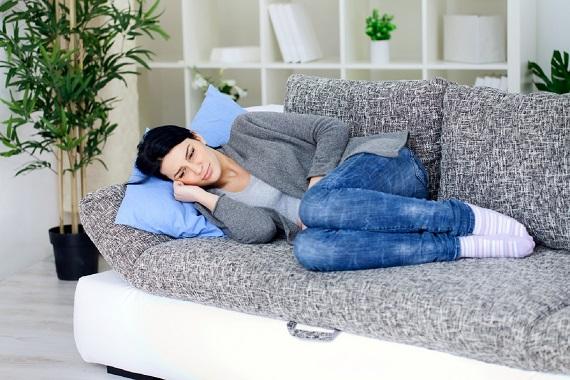 Femeie intinsa pe canapea, care are dureri abdominale