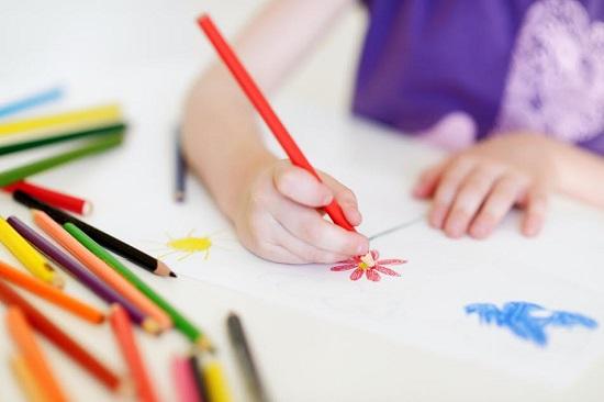 Copil ce coloreaza o floare