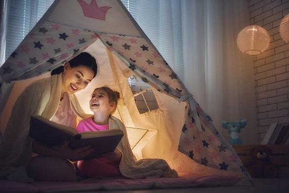 Mama ii citeste fiicei sale intr-un cort