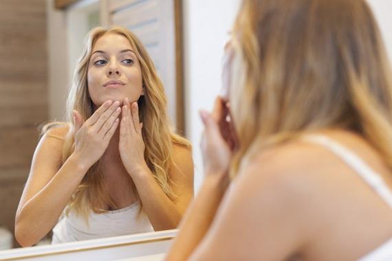 Fata ce isi examineaza tenul in oglinda