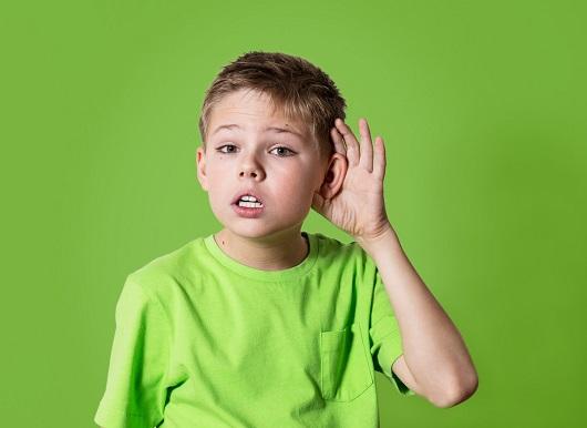 Baietel ce isi duce mana la ureche pentru a auzi mai bine