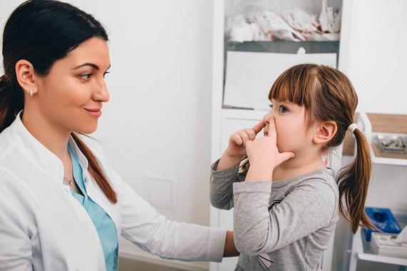 Fetita la un consult medical, tinandu-si manutele pe nas