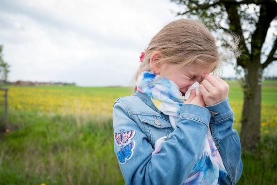 Fetita care are dureri sinusale si isi sufla nasul