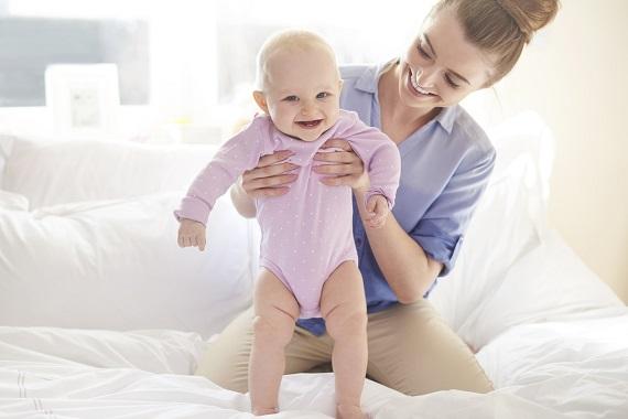 Mama ce isi tine bebelusul,astfel incat acesta sa stea in picioare