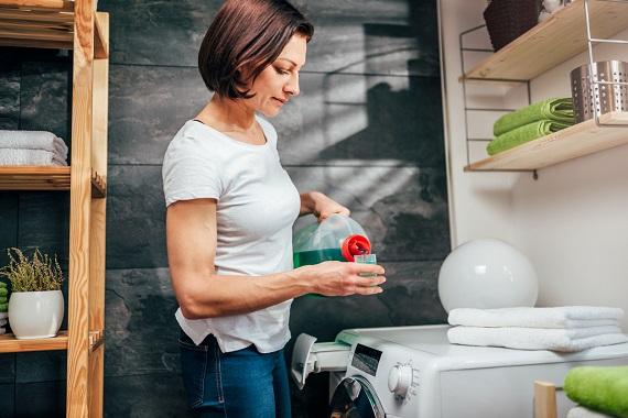 Femeie ce masoara cantitatea de detergent pe care o va introduce in masina de spalat