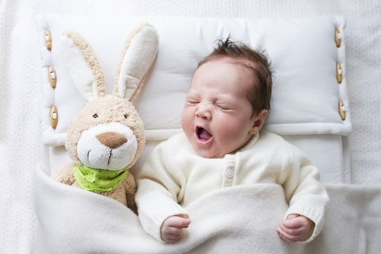 Bebelus culcat in pozitia pe spate, intr-un saculet de somn