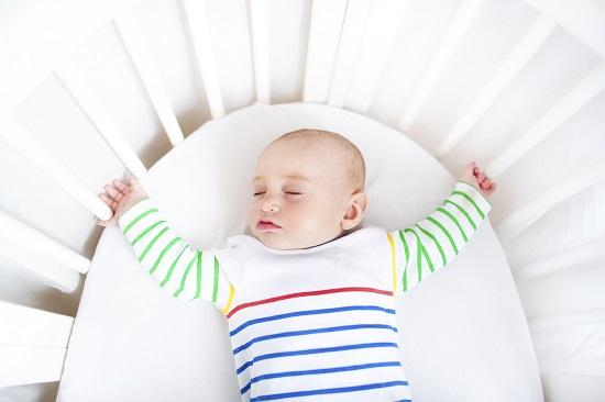 Bebelus doarme pe spate in patut